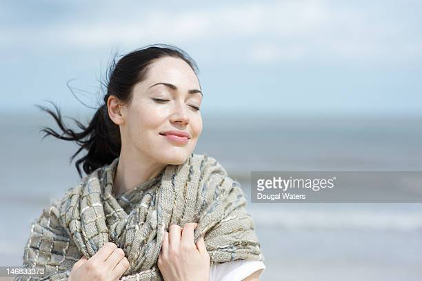 Woman at beach with eyes closed and smiling.
