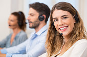Smiling female call centre operator doing her job with a headset while looking at the camera. Portrait of happy woman in a call center smiling and working. Portrait of happy smiling female customer su