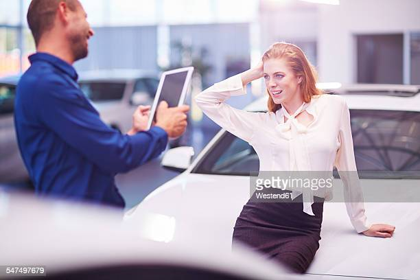 Woman at car dealer posing on bonnet for a photo
