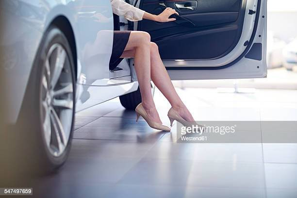 Woman at car dealer sitting in car