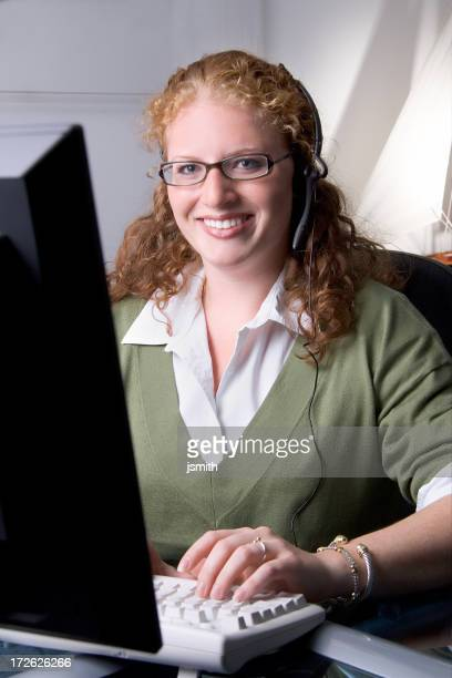Woman at computer smiling with headset