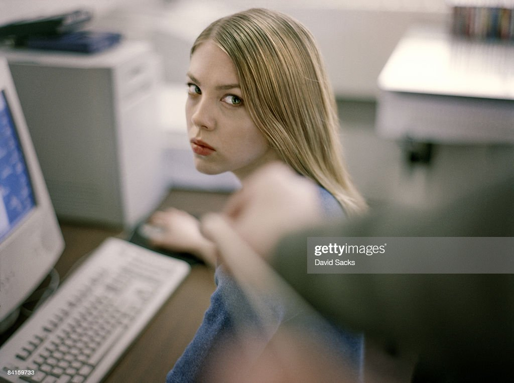 woman at desk giving dirty look to prankster.