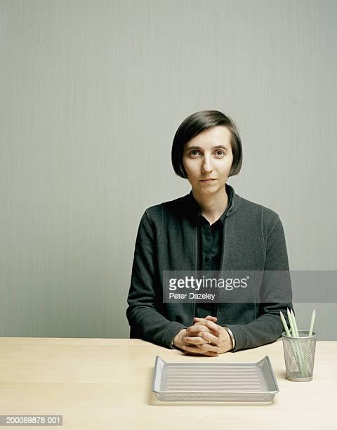 Woman at desk, hands clasped, portrait