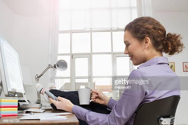 Woman at desk having a coffee break