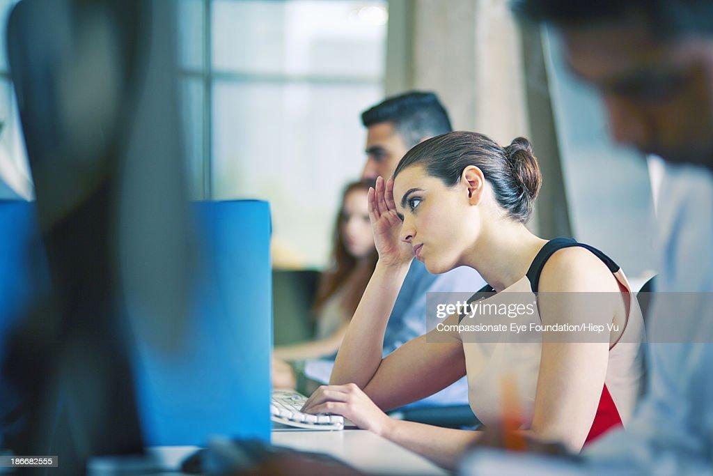 Woman at desk, staring at computer screen
