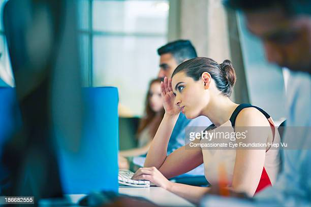 Woman at desk, staring at computer screen
