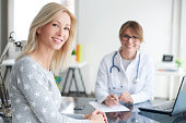 Shot of a beautiful mature womans sitting in doctor's office and cosulting with female doctor.