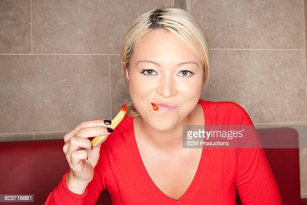 Woman at eafe eating french fries