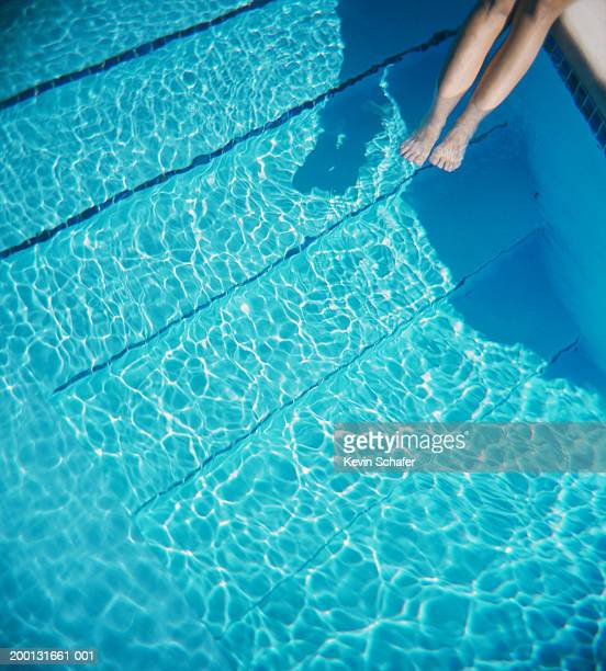 Woman at edge of pool, feet in water, low section, elevated view