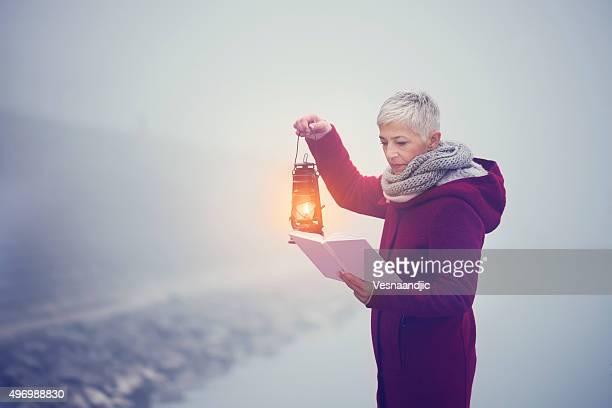 Frau im Nebel mit Laterne und buchen