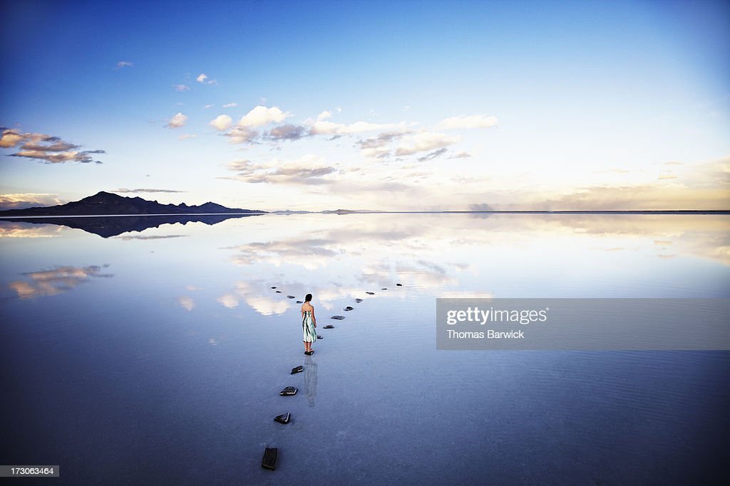 Woman at fork in stone pathway in lake at sunset : Stock Photo
