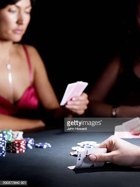 Woman at gaming table checking cards