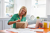 Woman At Home Addressing Package For Mailing