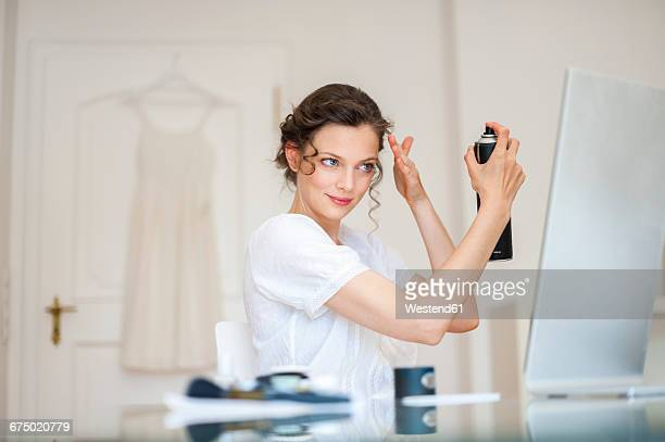 Woman at home doing her hair with hairspray