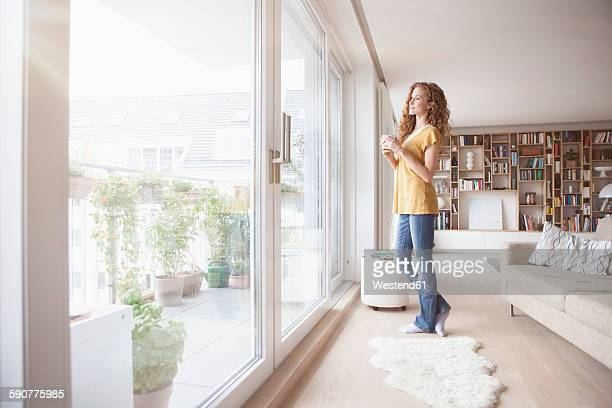 Woman at home looking out of window