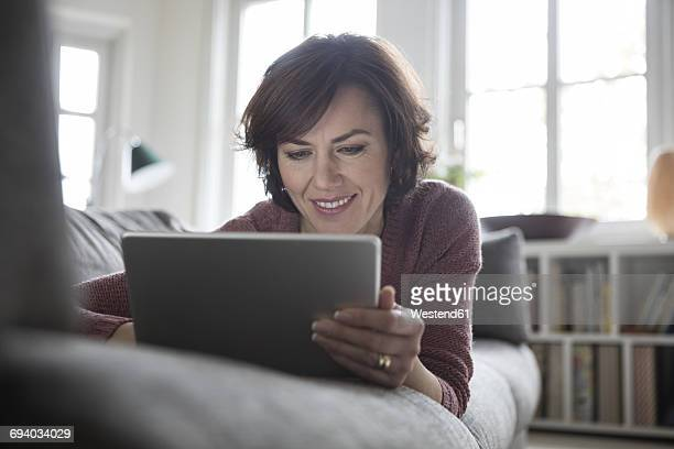 Woman at home lying on the sofa using tablet