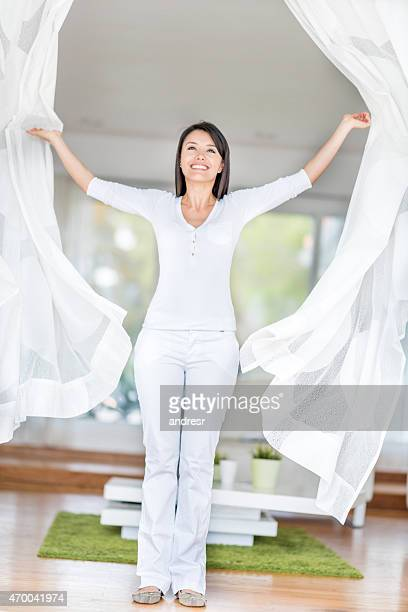 Woman at home opening the windows