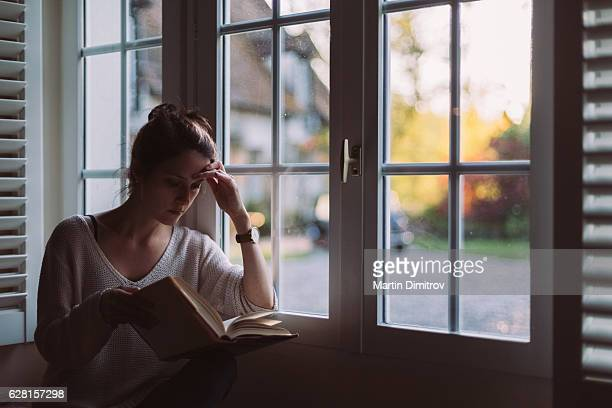 Woman at home reading a book