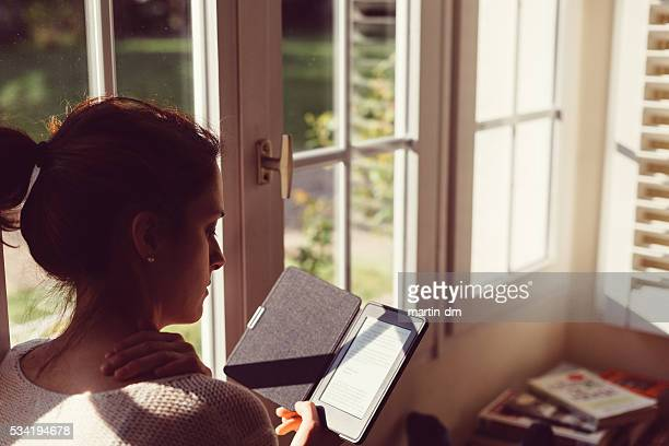 Mujer en casa, leyendo libro electrónico