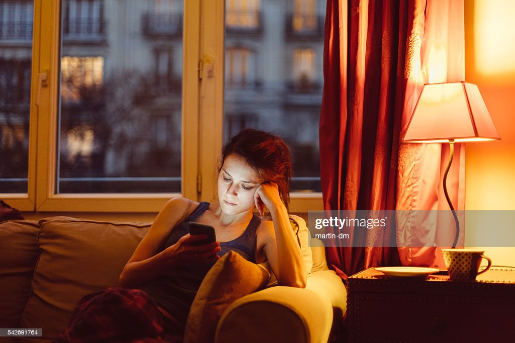 Woman at home texting on phone : Stock Photo