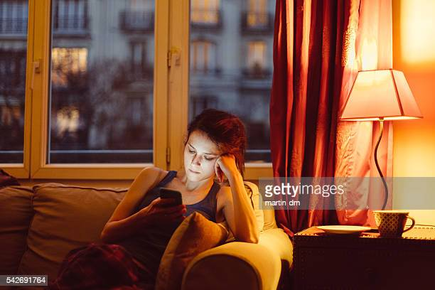 Woman at home texting on phone