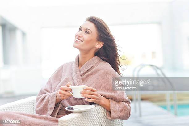 Woman at hotel poolside drinking coffee