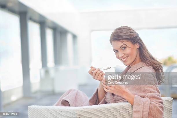 Woman at hotel poolside eating yogurt