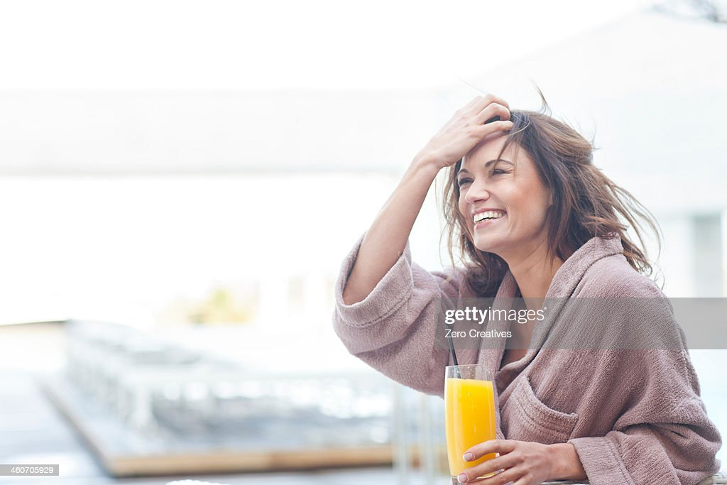 Woman at hotel poolside holding a glass of orange juice