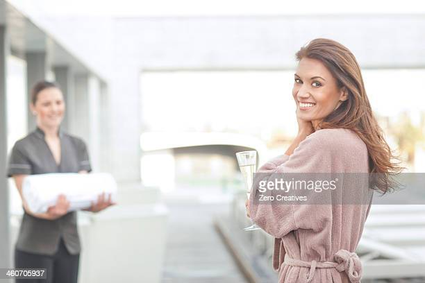 Woman at hotel poolside holding glass of champagne
