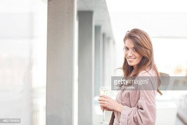 Woman at hotel poolside with glass of champagne