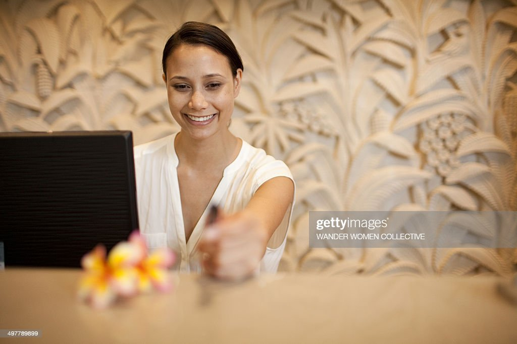 Woman at hotel reception desk smiling