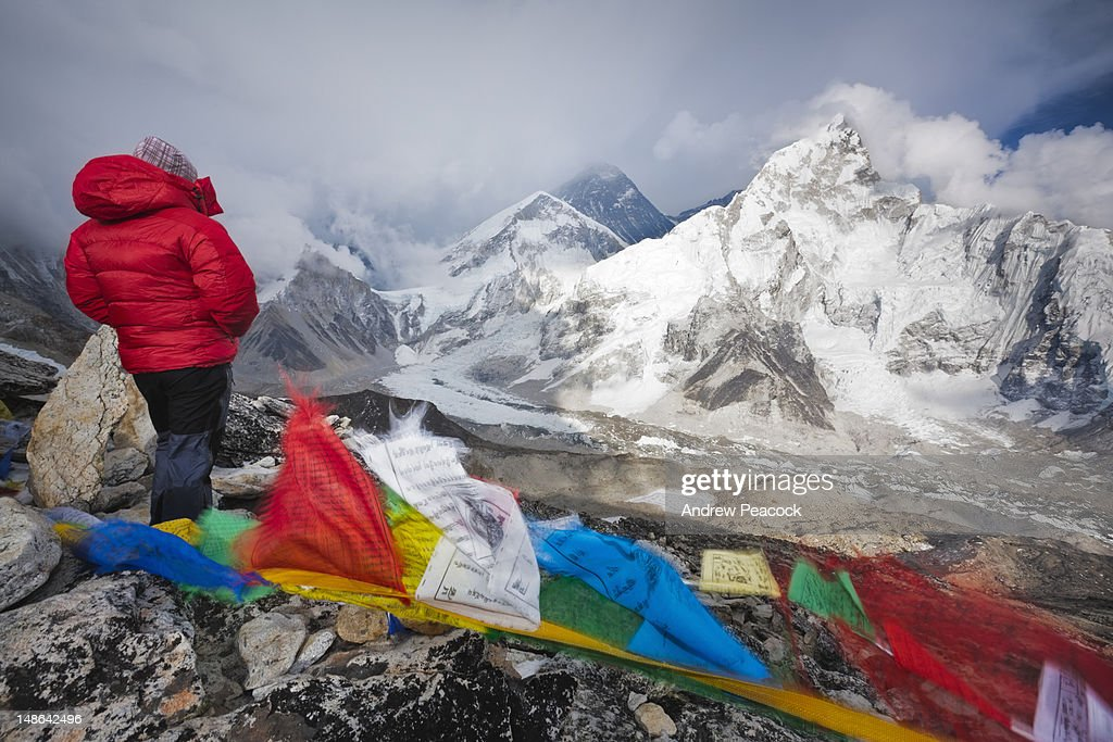 Woman at Kala Pattar on windy evening looking at snow storm engulfing Mt Everest. : Stock Photo