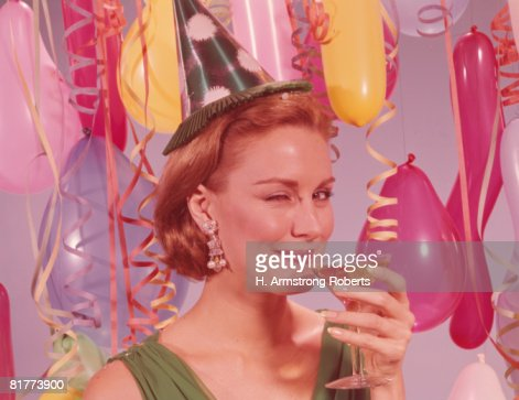 Woman at party, wearing party hat and winking, holding glass of wine. (Photo by H. Armstrong Roberts/Retrofile/Getty Images) : Stock Photo