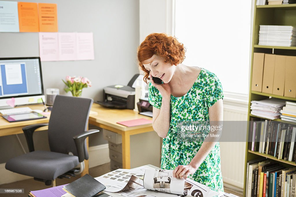 Woman at phone while looking at story boards. : Stock Photo