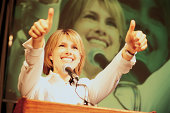 Woman at podium giving thumbs-up