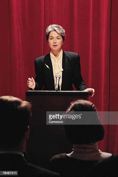 Woman at podium speaking to audience