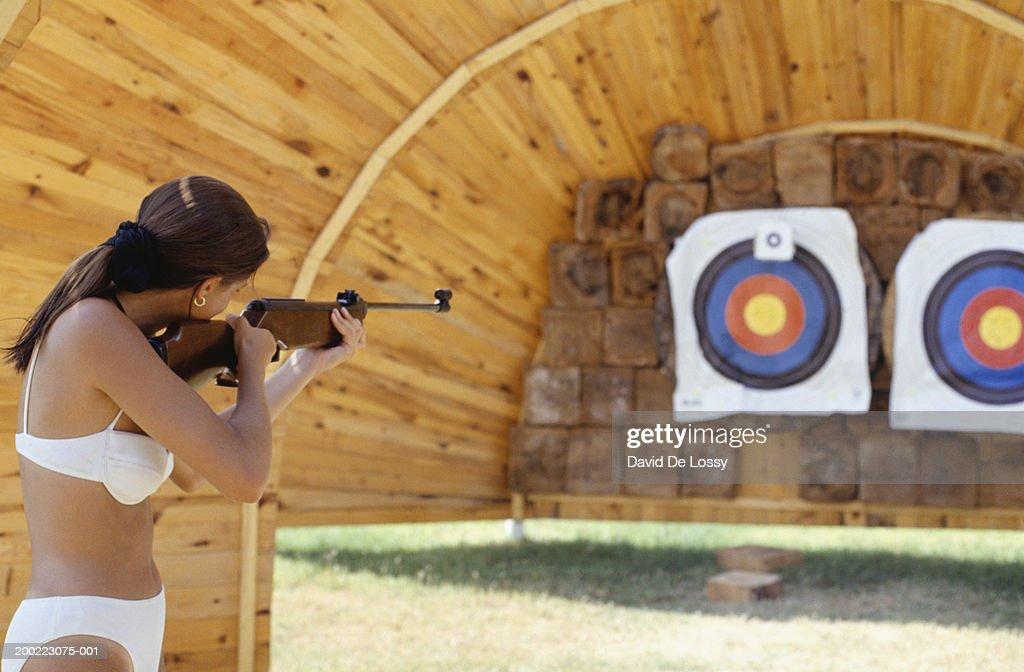 Woman at shooting range aiming rifle