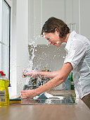 Woman at sink in domestic kitchen being drenched by broken tap, side view