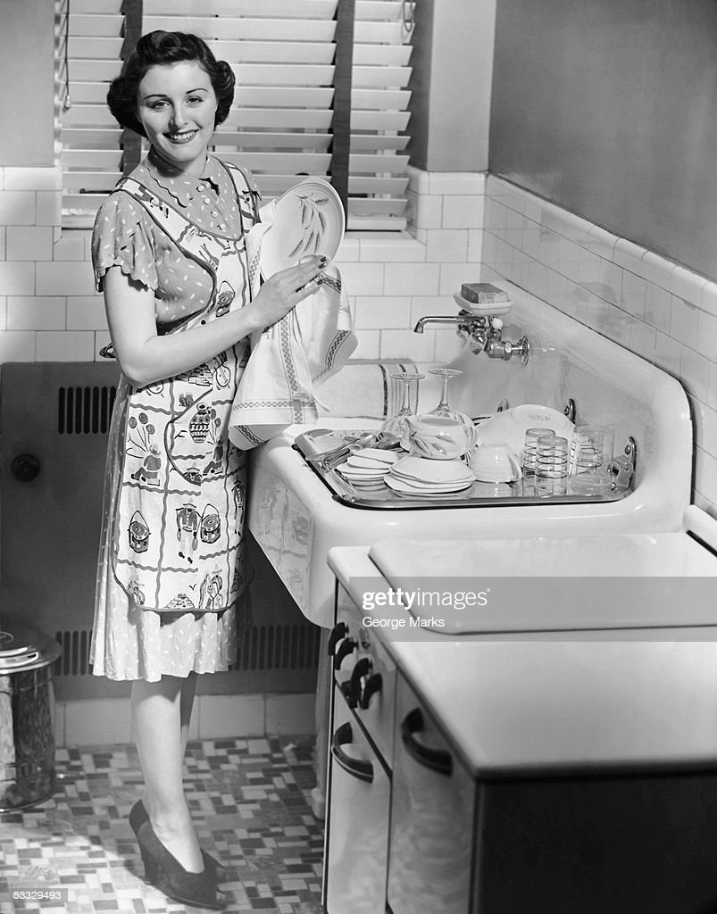 Woman at sink washing dishes : Stock Photo