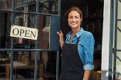 Portrait of a happy waitress standing at restaurant entrance. Portrait of mature business woman in black apron ready to attend new customers in her just opened coffee shop. Happy beautiful woman owner