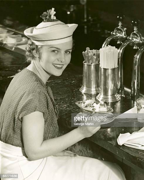 Woman at soda fountain with banana split