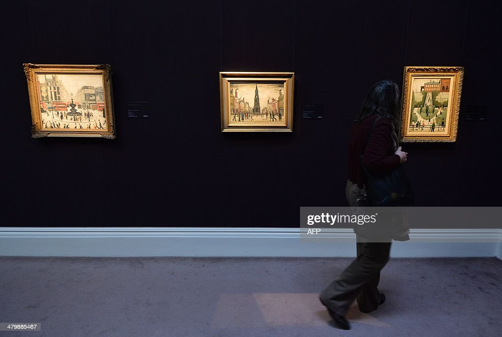 A woman at Sotheby's auction house in London on March 21, 2014 looks at works of art by British artist Laurence Stephen Lowry entitled 'Piccadilly Circus' 1959 (L) expected to realise GBP 2,000,000-3,000,000, 'Market Place, Berwick-Upon-Tweed' 1935 (C) expected to realise GBP 600,000-800,000 and 'Peel Park, Salford' 1944 (R) expected to realise GBP 400,000-600,000, all part of the Lowry , The A.J Thompson Collection sale.