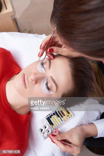 woman at spa salon applying false eyelashes