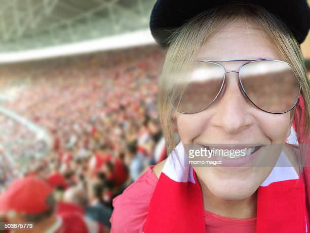 Woman at sports event, wearing scarf, smiling