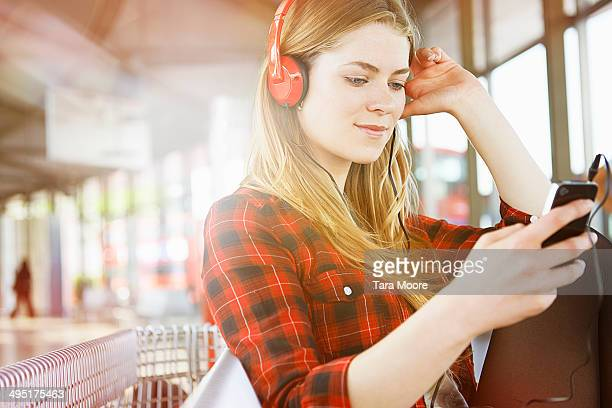woman at station listening to music with mobile