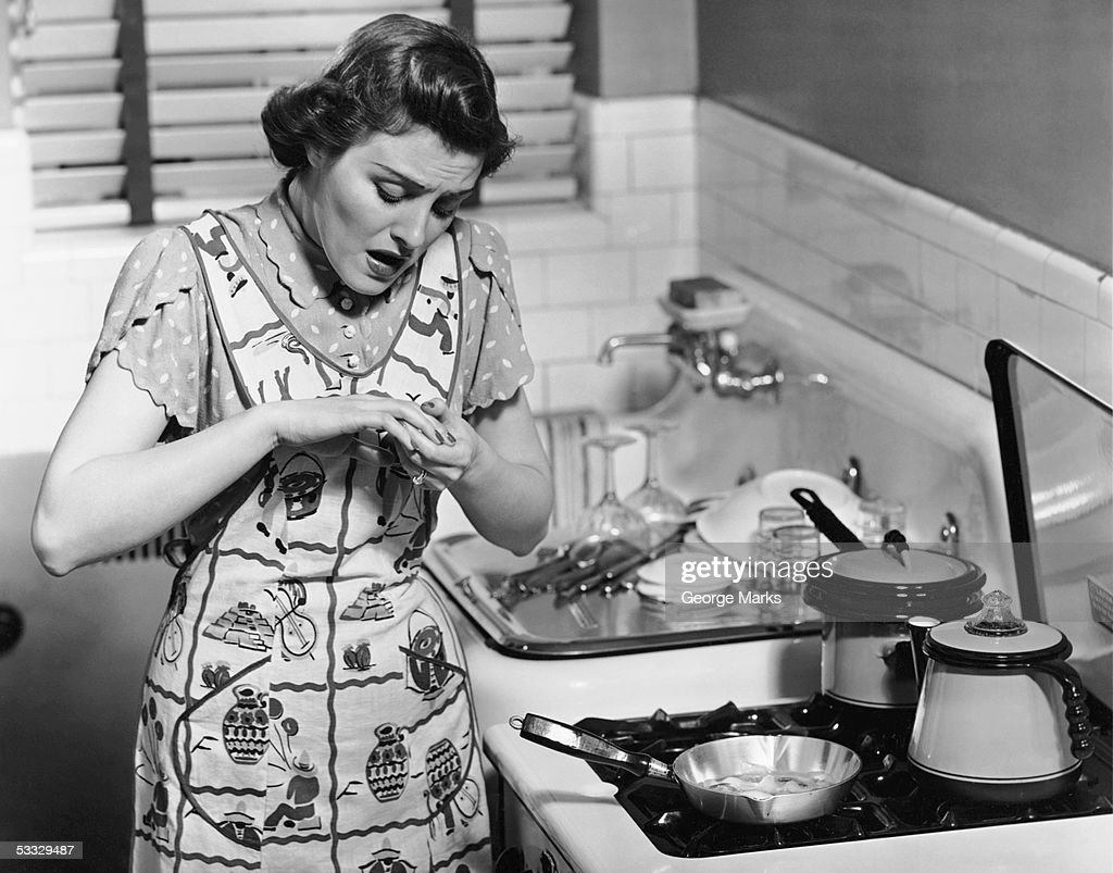 Woman at stove after burning hand : Stock Photo