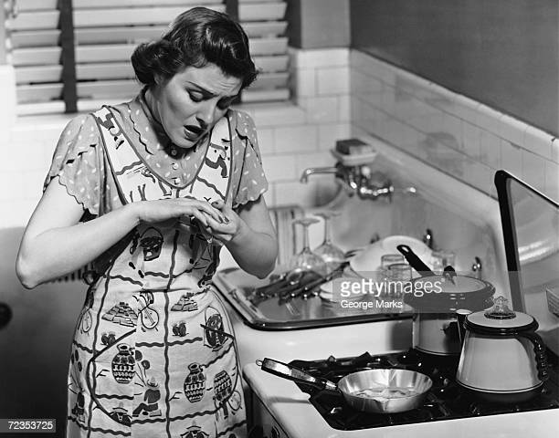 Woman at stove after burning hand