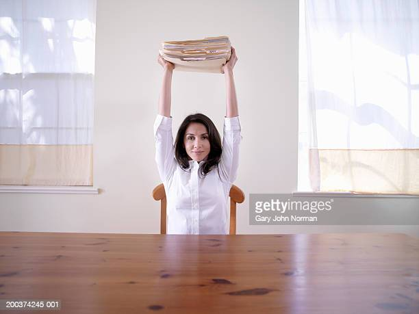 Woman at table holding stack of files over head, portrait