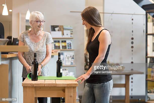Woman at table with bottles of wine smiling