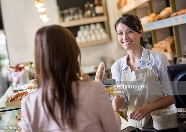 Femme à la boulangerie réglant par carte de crédit